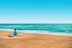 Surfista da jovem senhora que descansa e que espera ondas grandes para vir Fotografia de Stock Royalty Free
