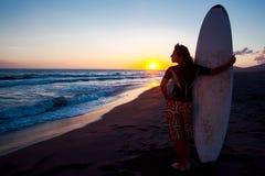 Surfista fêmea novo na praia no por do sol Foto de Stock
