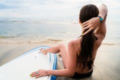 Surfista fêmea que senta-se ao lado da placa após surfar na praia imagens de stock