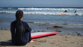 Surfista femminile che contempla le onde Fotografia Stock