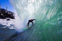 Surfista na câmara de ar larga com rochas Foto de Stock