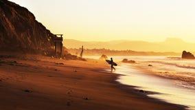 Surfista na praia no por do sol Imagens de Stock