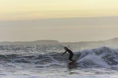 Surfista que aprecia nivelando a ressaca no mar áspero no crepúsculo fotos de stock royalty free
