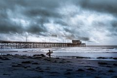 Surfista que espera na linha costeira que guarda sua placa em um dia nebuloso Fotografia de Stock Royalty Free