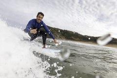 Surfista que tem o divertimento que trava uma onda e que cumprimenta fotos de stock