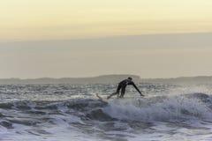 Surfista que toca na onda ao travar o equilíbrio durante o nivelamento da ressaca no mar áspero imagens de stock royalty free