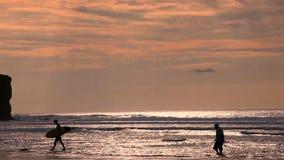 Surfista in siluetta che cammina con i bordi di spuma lunghi al tramonto sulla spiaggia tropicale archivi video
