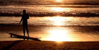 Surfista sulla spiaggia dell'oceano al tramonto Fotografie Stock Libere da Diritti