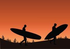 Surfistas do por do sol Fotografia de Stock Royalty Free