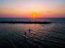 Surfistas do SUP que remam com por do sol imagens de stock royalty free