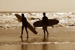 Surfistas em um litoral imagens de stock