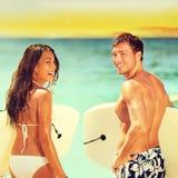 Surfistas na praia que tem o divertimento no verão Fotografia de Stock