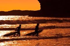 Surfistas que andam fora do mar Imagem de Stock