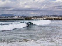 Surfistas que travam ondas em Costa da Caparica fotografia de stock royalty free
