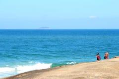 surfisti che camminano sulla pietra dal mare fotografia stock