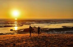Surfisti che entrano al tramonto Fotografie Stock Libere da Diritti