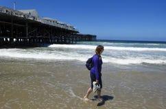 Surfisti di un Wacthes della donna come cammina spiaggia pacifica Fotografia Stock