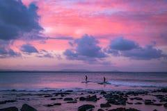 Surfisti sulle onde in oceano sotto il cielo variopinto fotografia stock libera da diritti