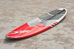 Surfplank en roeispaan op het zand bij het strand Stock Foto's