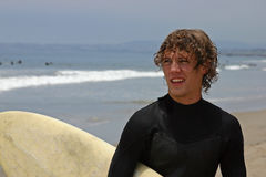 Surfs up. A handsome young man with his surfboard royalty free stock photo
