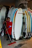 Surfshop Lady. A smiling black woman cleans a surfshop floor with many surfboards in the background at Muizenberg Beach, Cape Town, South Africa stock images