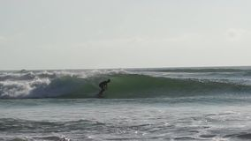 Surfujący w oceanu Bali wyspie, Indonezja Surfingowowie surfuje na surfboard na błękitnych dennych falach zbiory