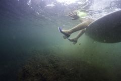Surfuje dziewczyny obsiadanie na surfboard z butami podwodnymi fotografia stock
