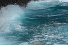 With the Surge. A closeup of a wave crashing ashore and the glassy water right behind it stock photography
