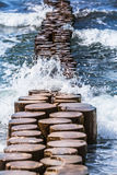 Surge at the Coast. Waves of splashing water of the sea break of a row of wooden groin royalty free stock image