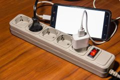 Surge Protector extender charges the phone smarfon. Extension cord with five outlets stock image