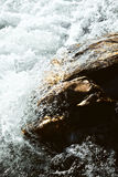 Surge. Sparkling wild water rushing up a stone Royalty Free Stock Image