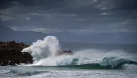 The Surge. A winter wave smashes into the shore at Plettenberg bay, South Africa stock image