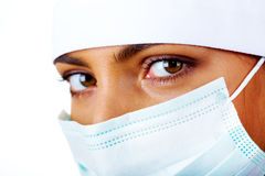 Surgeon. Close-up of pretty assistant in mask looking at camera Stock Photo