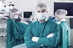 Surgeon. With arms crossed looking at camera with colleagues performing in background Royalty Free Stock Photo
