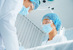 Surgeon and assistant in operating room. Man surgeon and assistant working in operating room, teamwork. Focus on women assistant Stock Photography