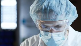 Surgeon assistant preparing patient and medical equipment for operation closeup. Stock video Royalty Free Stock Image