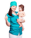 Surgeon with a baby. Portrait of a surgeon holding a  baby and his thumb up, isolated against white background Royalty Free Stock Image
