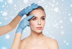 Surgeon or beautician hands touching woman face. People, cosmetology, plastic surgery and beauty concept - surgeon or beautician hands touching woman face over Stock Image