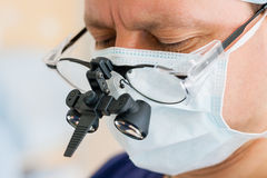 Surgeon with binocular glasses stock images