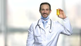 Surgeon with bottle of pills. Handsome smiling medical doctor holding prescription pill bottle on blurred background stock video footage