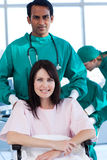 Surgeon carrying a female patient on a wheelchair. Ethnic surgeon carrying a female patient on a wheelchair in a hospital Stock Photography