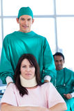 Surgeon carrying a patient on a wheelchair. Attractive surgeon carrying a patient on a wheelchair in a hospital Royalty Free Stock Photos
