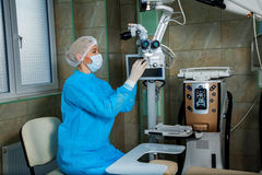 Surgeon checks the operating microscope before surgery Royalty Free Stock Images