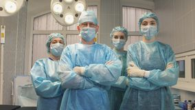 Portrait of a surgeon team after a successful operation. The surgeon crosses his arms with a team of nurses in the operating room Stock Images