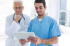 Surgeon and doctor discussing over digital tablet Royalty Free Stock Images