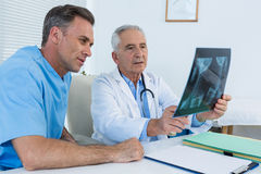 Surgeon and doctor discussing x-ray report. In clinic Royalty Free Stock Photography