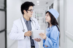 Surgeon and doctor holds tablet in corridor Stock Image