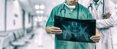 Surgeon and doctor looking at x-ray film. Doctor and surgeon examining xray film, diagnose patient `s waist bone injury. Surgery operation and medical banner Royalty Free Stock Photos