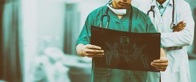 Surgeon and doctor looking at x-ray film. Doctor and surgeon examining xray film, diagnose patient `s waist bone injury. Surgery operation and medical banner Stock Images