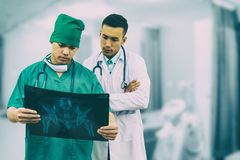 Surgeon and doctor looking at x-ray film. Doctor and surgeon examining xray film, diagnose patient `s waist bone injury. Surgery operation and medical concept Royalty Free Stock Photography
